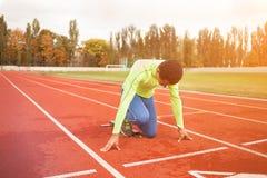 Le jeune homme sportif sont prêt à fonctionner sur le champ de courses Personnes bien formées convenables au grand stade moderne  Photos libres de droits
