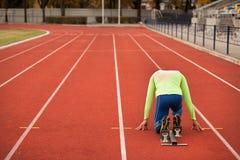 Le jeune homme sportif sont prêt à fonctionner sur le champ de courses Personnes bien formées convenables au grand stade moderne  Photo libre de droits