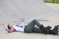 Le jeune homme sur des patins de rouleau a eu un accident, il est tombé vers le bas et hur Photos stock