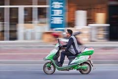 Le jeune homme sur un e-vélo passe une boutique, Hengdian, Chine Photo libre de droits