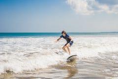 Le jeune homme, surfer de débutant apprend à surfer sur une mousse de mer sur le B photographie stock