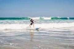 Le jeune homme, surfer de débutant apprend à surfer sur une mousse de mer sur le B photos libres de droits