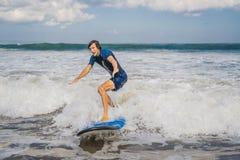 Le jeune homme, surfer de débutant apprend à surfer sur une mousse de mer sur le B image stock