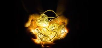 Le jeune homme tenant des coeurs a formé des lumières de ficelles à disposition images libres de droits