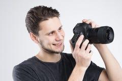 Le jeune homme tenant l'appareil-photo dans la chemise noire a isolé le studio Photo stock