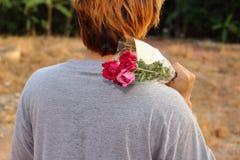 Le jeune homme tenant un beau bouquet des roses rouges au-dessus de l'épaule sur la nature a brouillé le fond Photo stock