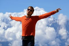 Le jeune homme tient, a répandu ses bras au loin, contre le contexte du massif d'Annapurna nepal Images libres de droits