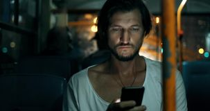 Le jeune homme tient le smartphone tout en voyageant en autobus la nuit Mâle barbu dans des écouteurs avec le téléphone, écran ta banque de vidéos