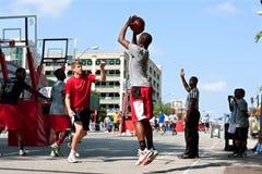 Le jeune homme tire le tir en suspension dans le tournoi de basket-ball de rue Photographie stock libre de droits