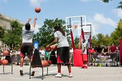 Le jeune homme tire trois indicateurs dans le tournoi extérieur de basket-ball de rue Image libre de droits