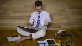 Le jeune homme travaille à la maison dans le pantalon de pyjama clips vidéos