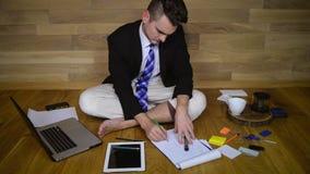 Le jeune homme travaille à la maison dans le pantalon de pyjama banque de vidéos