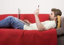 Le jeune homme travaille sur l'ordinateur portatif Image libre de droits