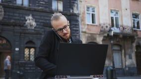 Le jeune homme travaille sur un ordinateur et parle au téléphone banque de vidéos