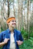 Le jeune homme trimarde dans la forêt photographie stock