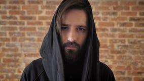 Le jeune homme triste avec la barbe dans le capot observe à l'appareil-photo, concept émotif, fond de brique banque de vidéos