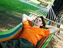 Le jeune homme a un repos dans un hamac Image libre de droits