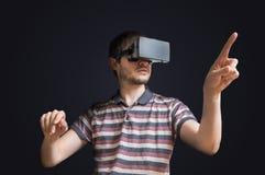 Le jeune homme utilise le casque de la réalité virtuelle 3D et touche quelque chose Images stock