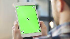 Le jeune homme utilise le smartphone avec greenscreen pour la communication banque de vidéos