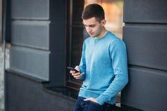 Le jeune homme utilise le téléphone sur la rue Support beau de type devant la fenêtre images libres de droits