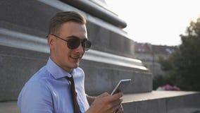 Le jeune homme vérifie son téléphone se tenant sur la rue banque de vidéos