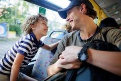Le jeune homme va en l'autobus ainsi que le fils photo stock