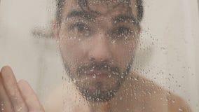 Le jeune homme verse l'eau sur le verre de la carlingue de douche dans au ralenti clips vidéos
