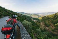 Le jeune homme voyage sur une moto arrêtée à un point de vue et à regarder la vallée de Douro Photographie stock libre de droits