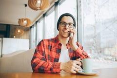 Le jeune indépendant attirant s'assied en café photo libre de droits