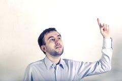 Le jeune indépendant masculin non rasé de programmeur recherche et montre le sien doigt-trouvé une solution après la pensée images stock