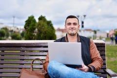 Le jeune indépendant masculin travaille avec l'ordinateur portable dans la rue sur le banc photographie stock