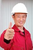 Le jeune ingénieur, l'ouvrier dans l'uniforme rouge. Image stock