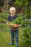 Le jeune jardinier blond montre fièrement sa récolte photos stock