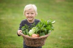 Le jeune jardinier blond montre fièrement sa récolte photographie stock