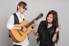Le jeune jeu de musiciens et chantent sur la guitare Photographie stock libre de droits
