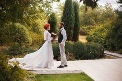 Le jeune jeune marié regarde tendrement sa belle jeune mariée Photos libres de droits