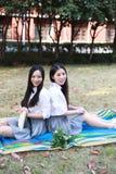 Le jeune joli costume chinois asiatique d'étudiant d'usage de filles à l'école a lu le sourire de rire de livre dans le jardin de photo libre de droits