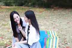 Le jeune joli costume chinois asiatique d'étudiant d'usage de filles à l'école mangent de la glace dans le jardin de nature photo stock