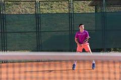 Le jeune joueur de tennis se prépare à recevoir les servis image libre de droits