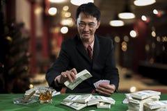 Le jeune joueur met des paris dans les piles du billet de banque images libres de droits