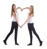 Le jeune jumelle des soeurs faisant la forme de coeur avec des bras Images stock
