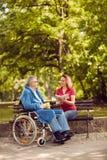 Le jeune livre de lecture de femme de soignant en parc a désactivé l'homme dans la roue Photographie stock libre de droits