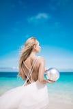 Le jeune long usage blond de jeune mariée de cheveux une robe et un support de mariage blancs de dos nu sur le sable blanc échoue Photographie stock