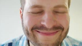 Le jeune mâle aux yeux bleus élégant avec une barbe regarde dans la caméra et clignote rapidement ses yeux, amour, plan rapproché banque de vidéos