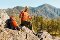 Le jeune mâle avec la barbe voyage par la montagne, sac à dos de touristes se tenant sur la colline de roche tout en appréciant l photographie stock libre de droits