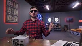 Le jeune mâle barbu donne cinq à la caméra ayant la boîte d'alimentation d'énergie sur le bureau banque de vidéos