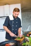 Le jeune, mâle, dans la cuisine, coupe les oignons verts image stock