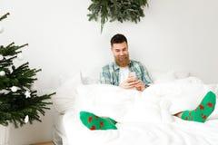 Le jeune mâle gai avec la longue barbe épaisse, porte les chaussettes colorées, s'assied dans le lit et utilise le téléphone inte Image stock