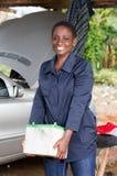 Le jeune mécanicien féminin soulève une batterie de voiture Photos stock