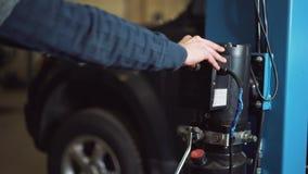 Le jeune mécanicien professionnel soulève la voiture sur l'ascenseur pour exécuter le diagnostic du châssis clips vidéos
